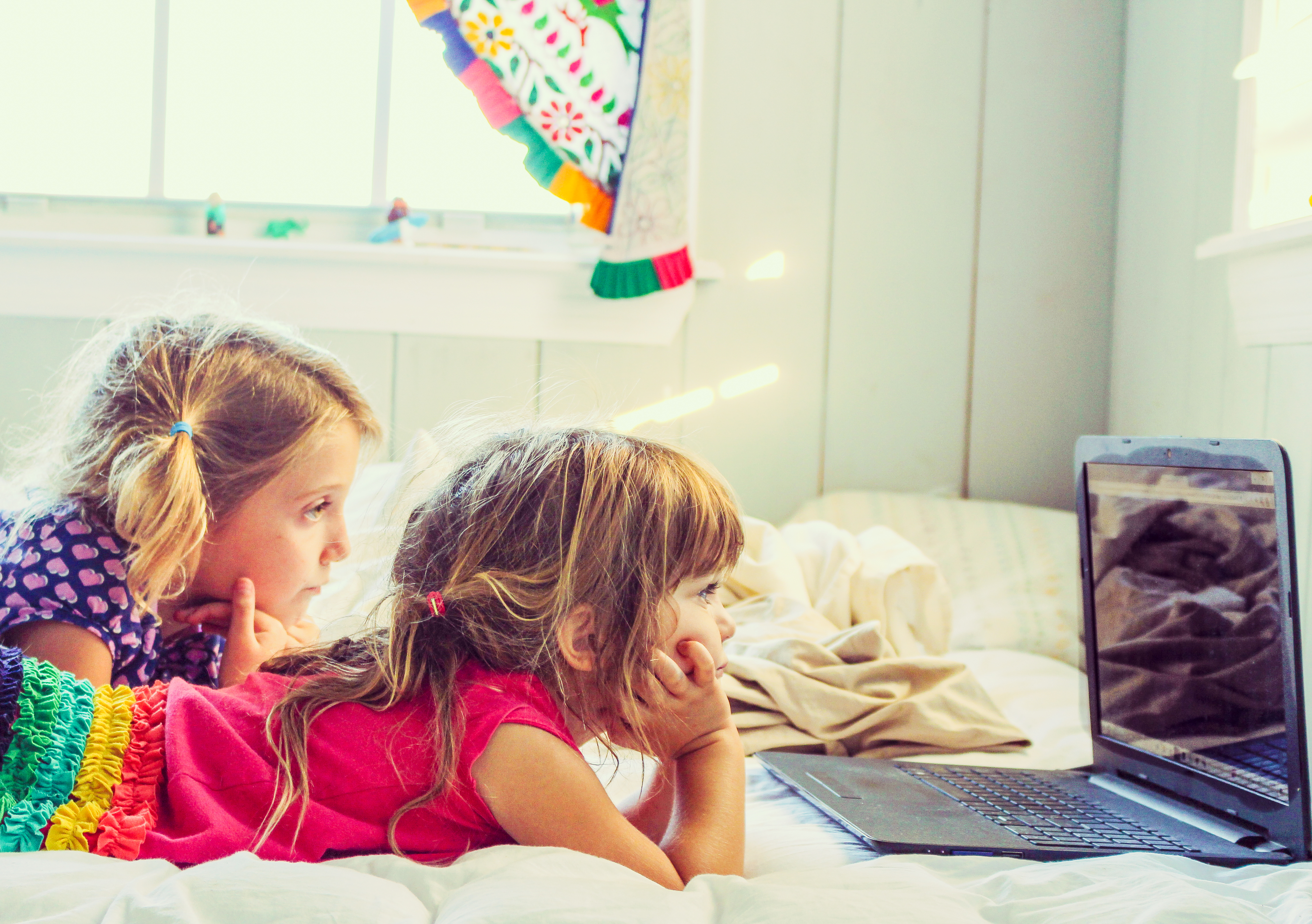 Two Young Girls Watching Television on a Laptop Computer